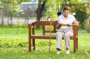 elderly woman reading on a bench outside
